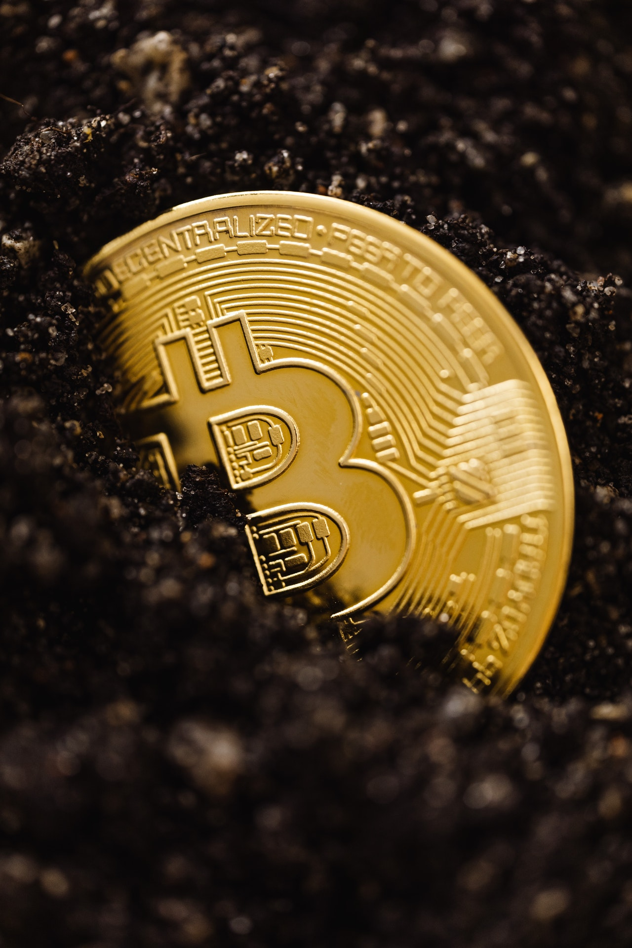 A bitcoin lying partially covered, in dirt